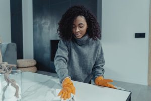 A woman disinfecting a table before she starts to clean and fix damaged items after moving