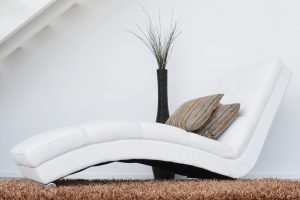 Two pillows on a white leather fainting couch.