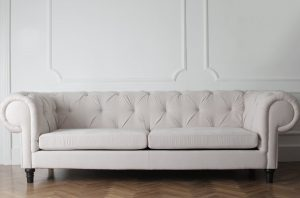 A white upholstered couch, representing how to clean different types of furniture.