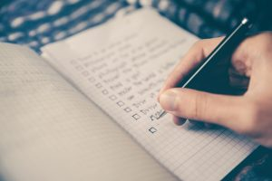 a hand making a checklist in a notebook
