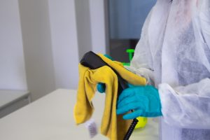 a professional cleaner in a protective suit cleaning