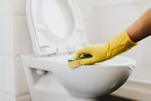 A person cleaning a toilet bowl