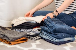 a woman sorting out clothes and decluttering