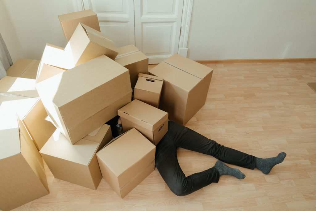 A man lying under a pile of boxes.