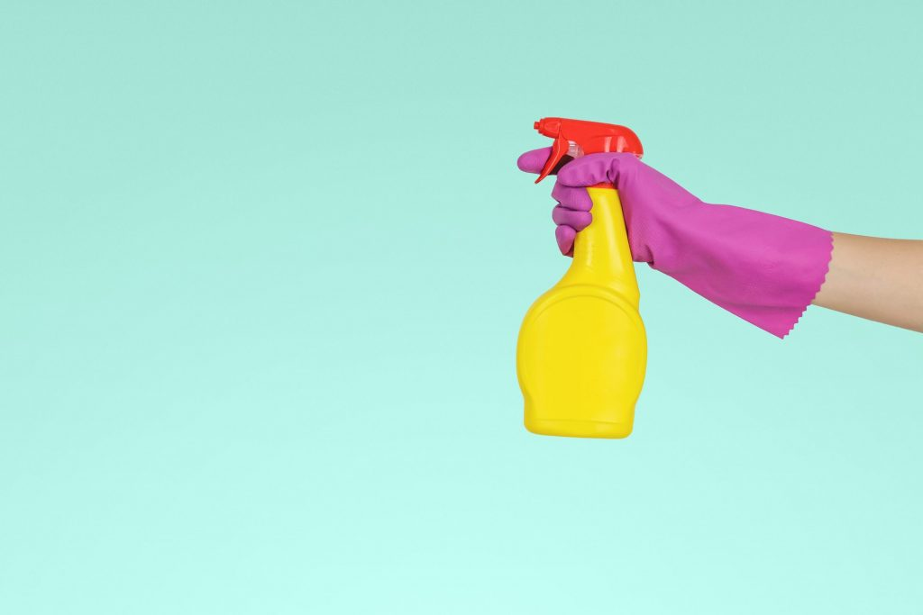 A person holding a spray bottle before cleaning their home after a major renovation project.